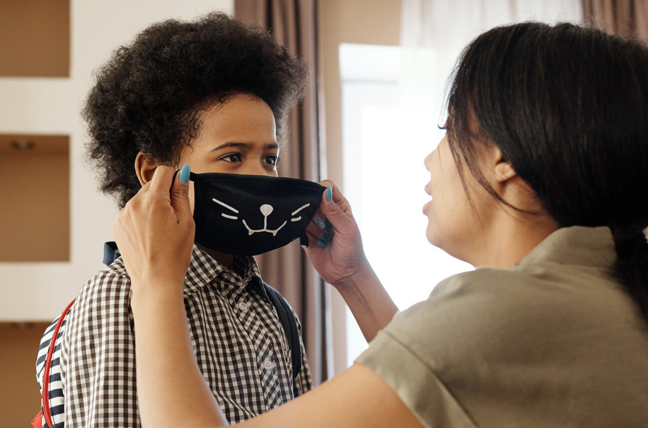 Mother putting face mask on her son to stay safe from COVID-19