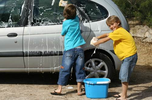 Two kids washing their parents car for allowance