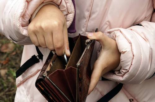 A child putting pocket change in her purse
