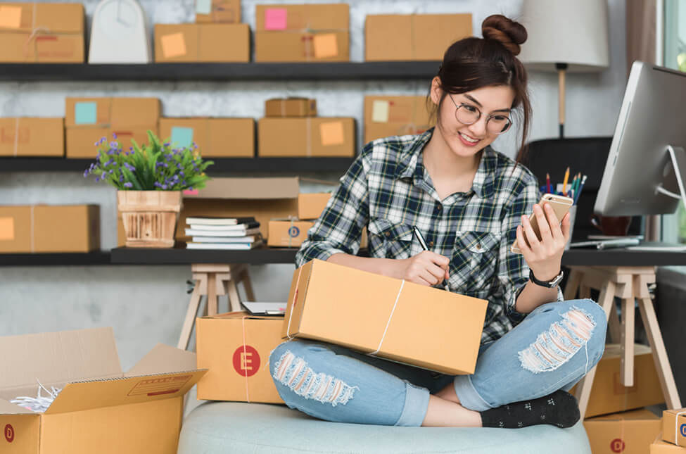 A teenage girl packing boxes for her dropshipping business