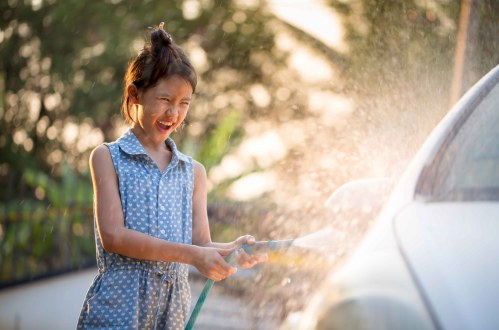 A young girl washing her parents car for allowance