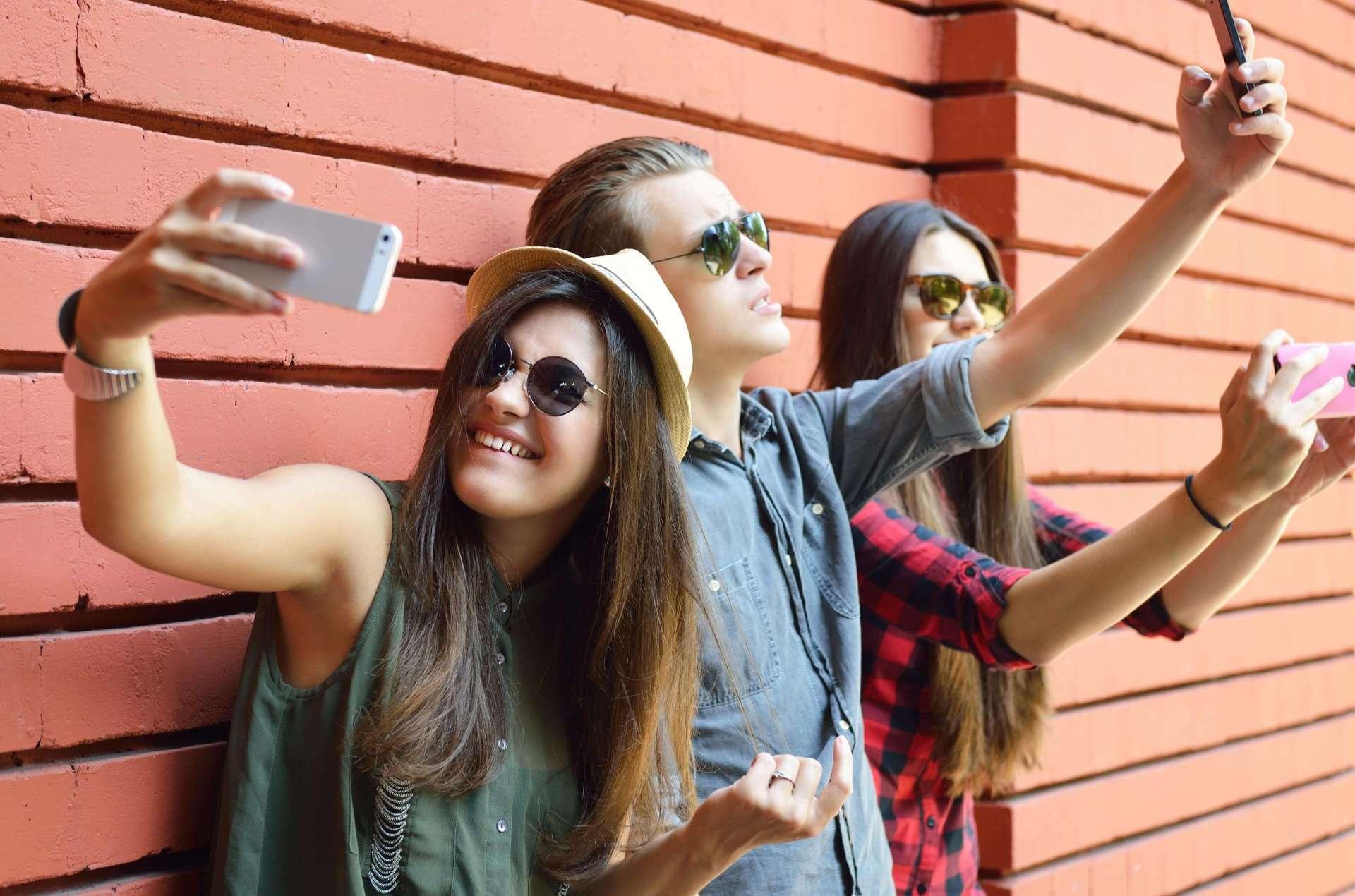 Teenagers taking selfies for social media