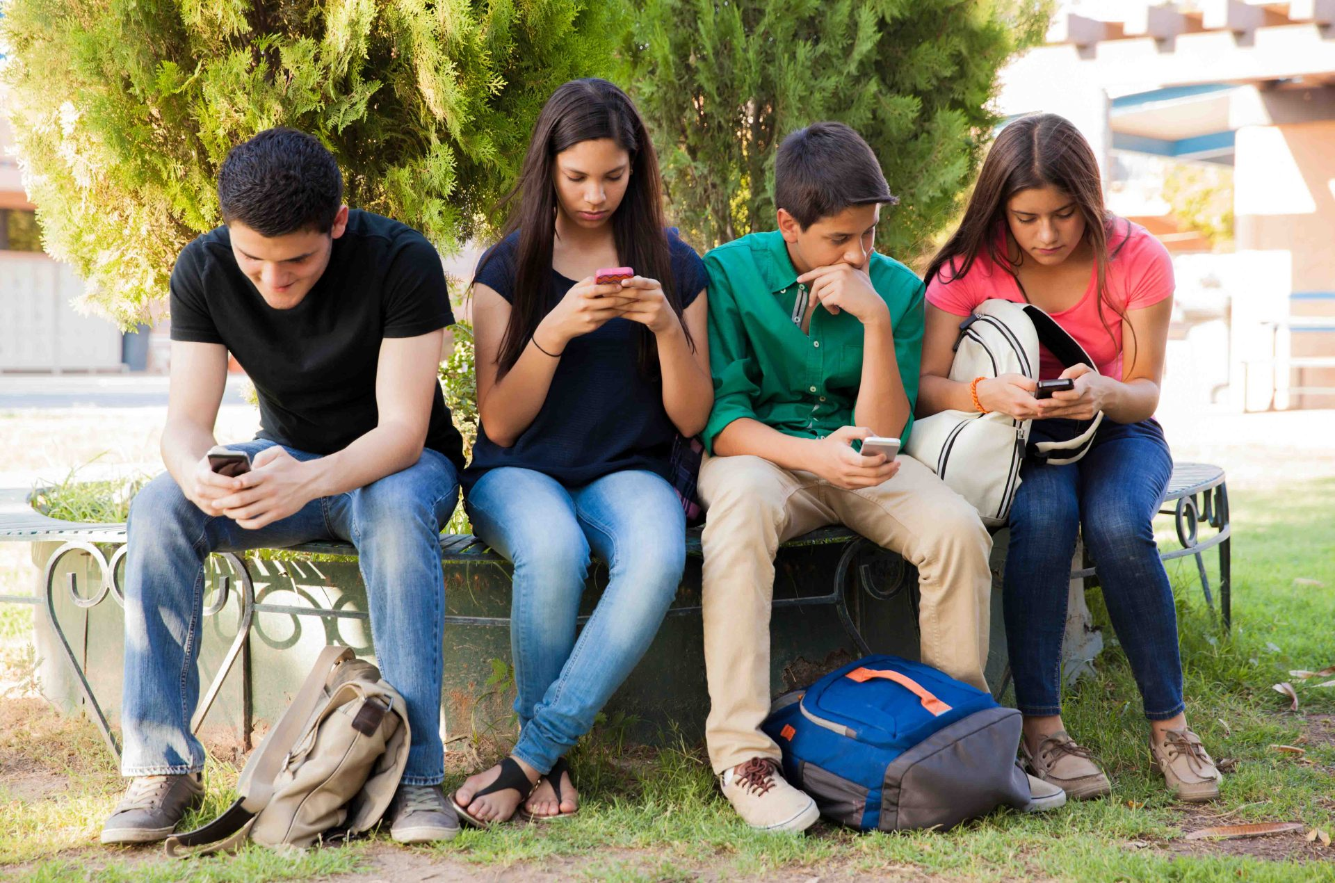 A group of teenagers hanging out and using the Mydoh money management app