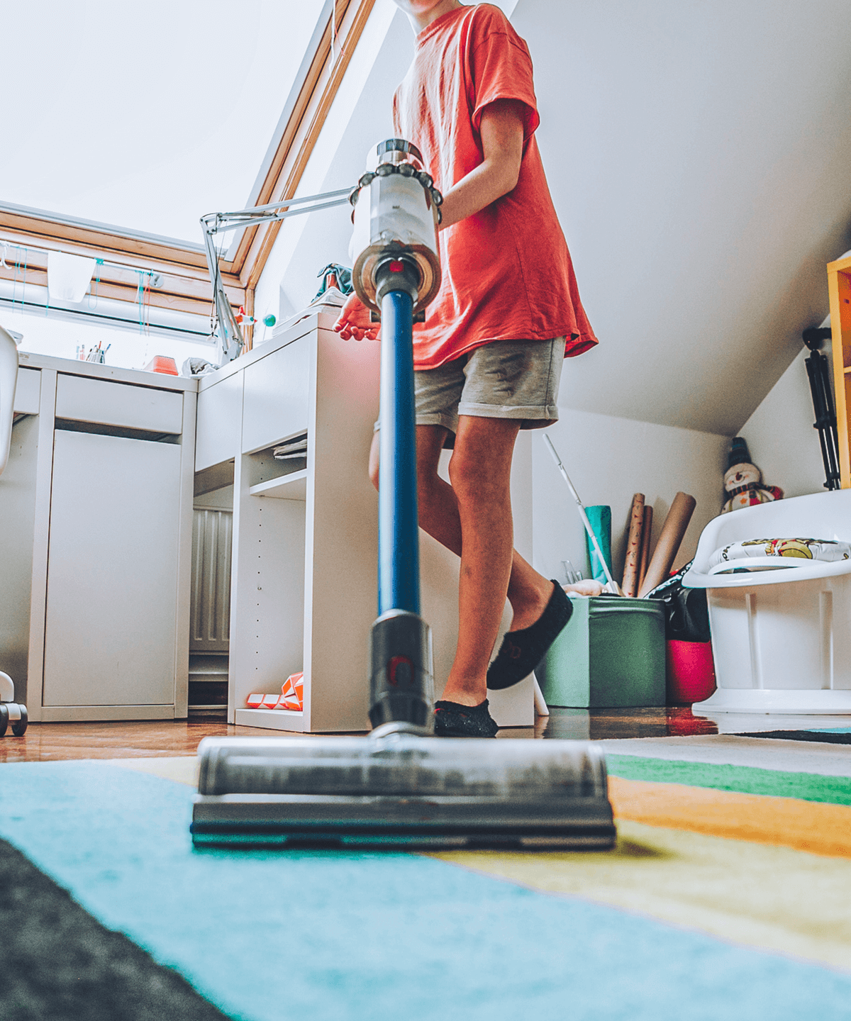 A teenager vacuuming his room with a Dyson vacuum