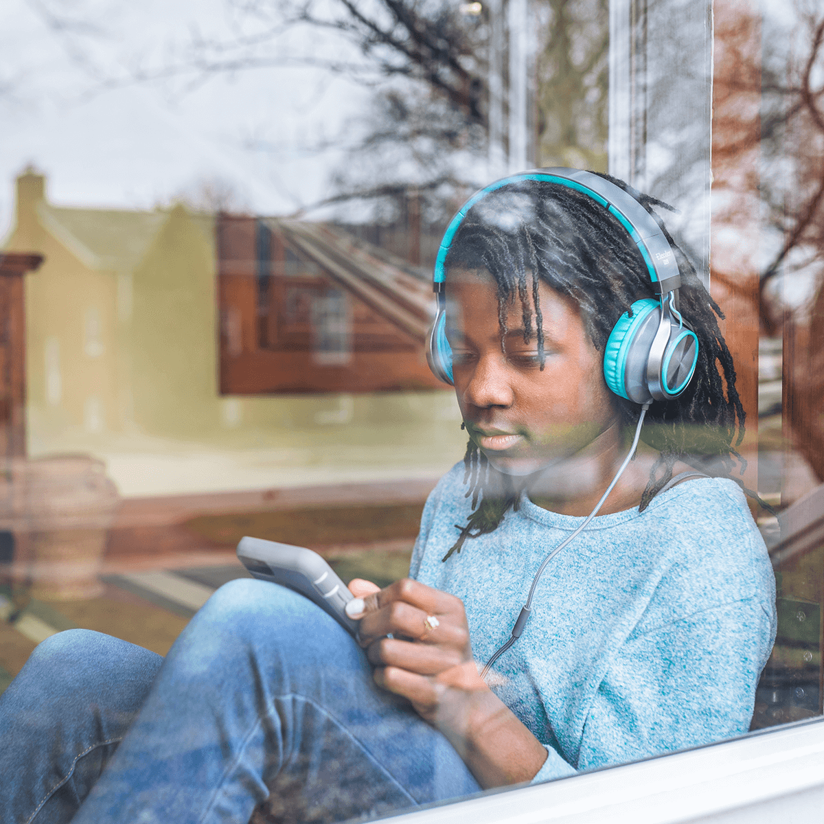 A young teenage boy listening to music on his mobile phone