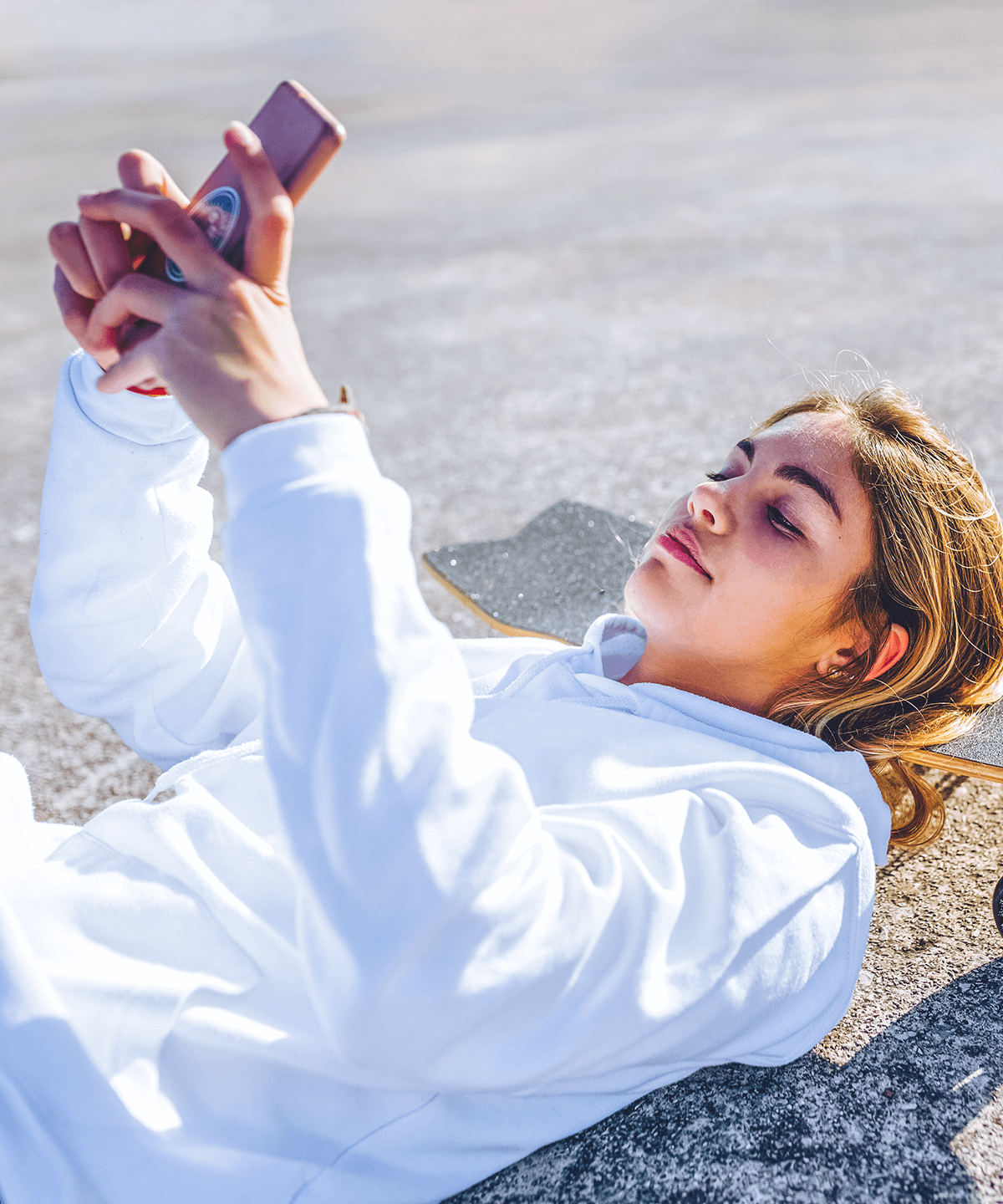 A teenage girl laying down on a skateboard using the Mydoh app on her phone