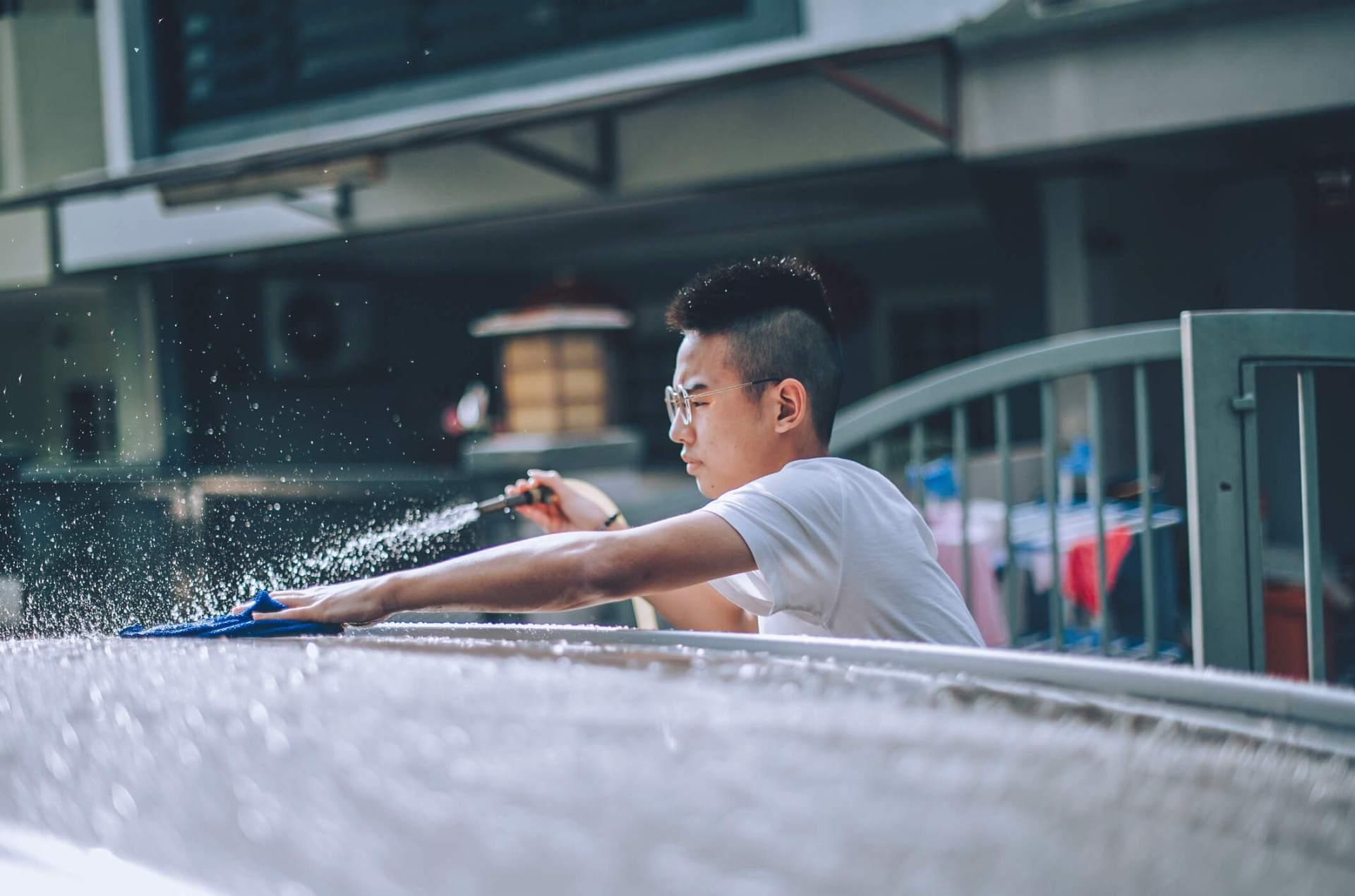 A teenager washing his parents car