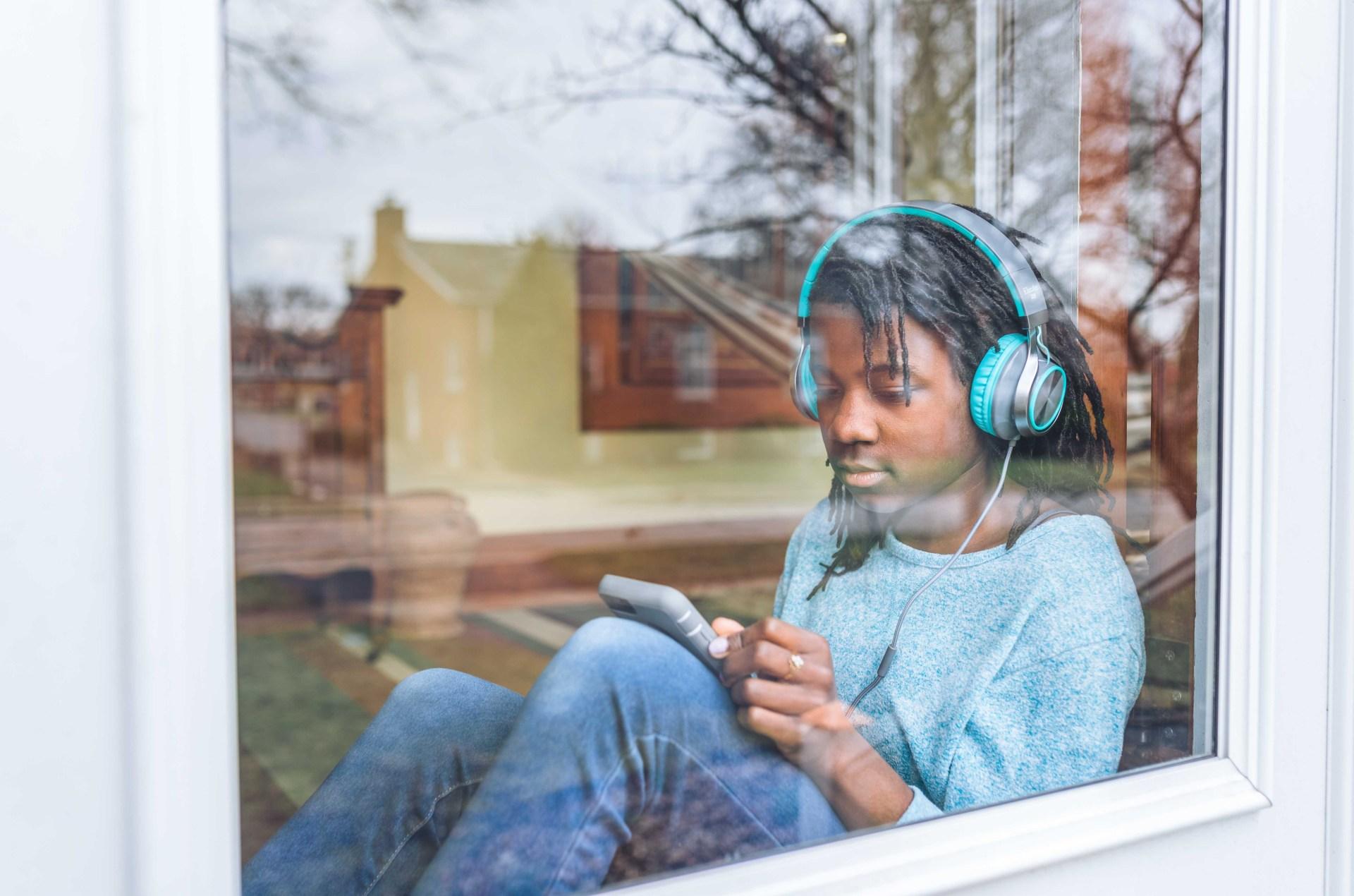 teen wearing headphones looking at phone
