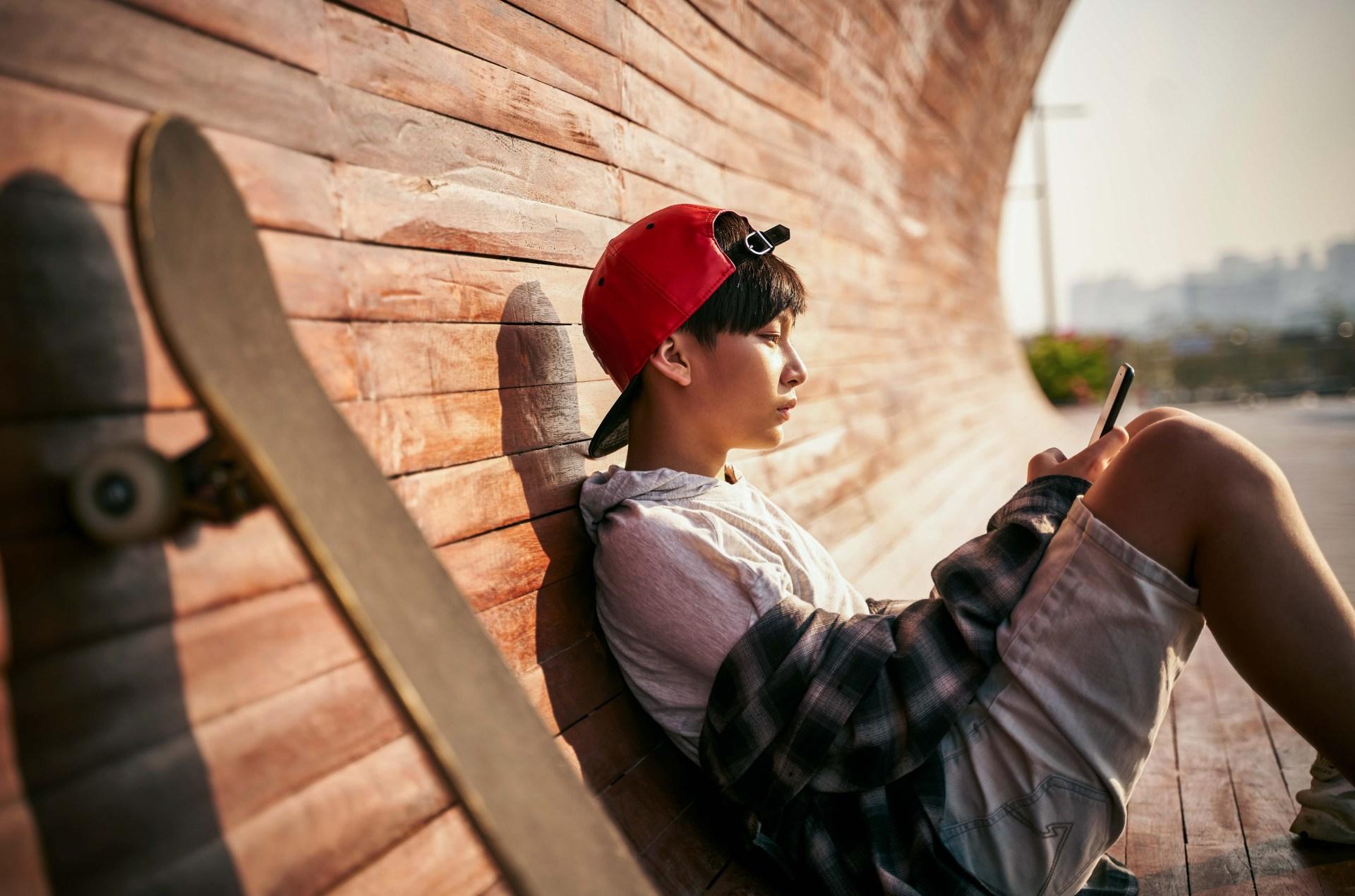 teen boy with skateboard on phone