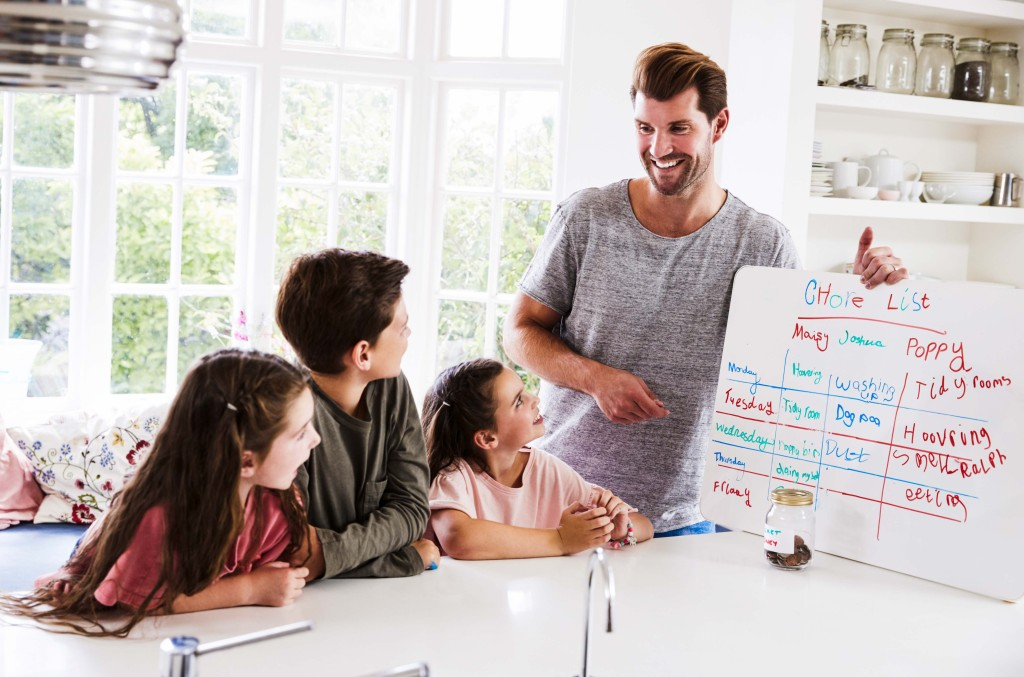 father with kids chore board